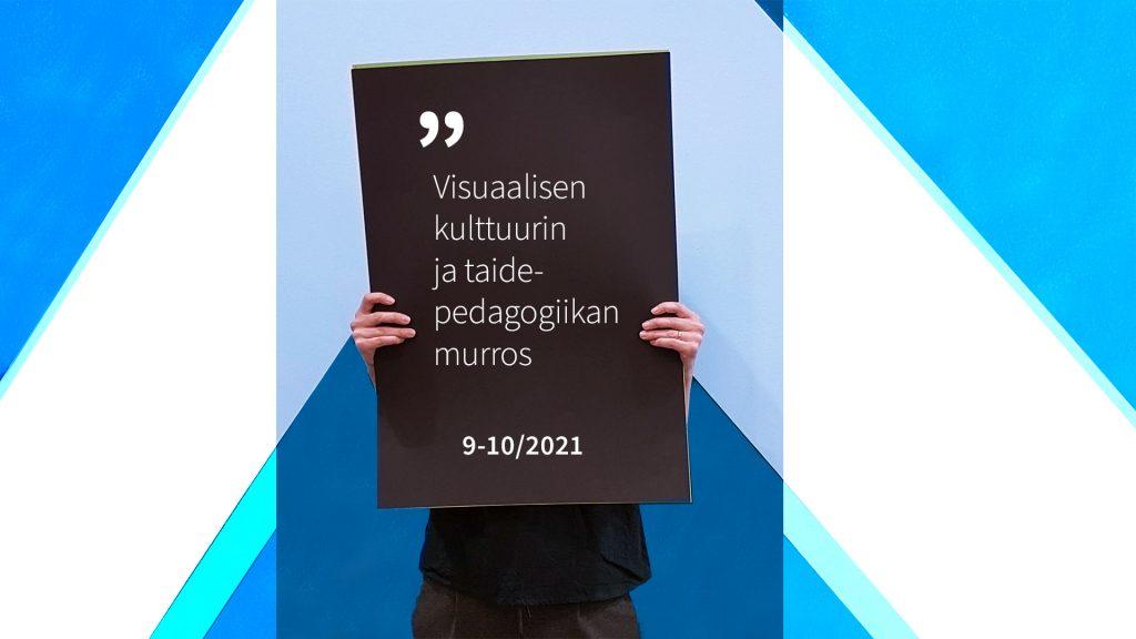 Henkilö pitää käsissään kylttiä, jossa lukee Visuaalisen kulttuurin ja taidepedagogiikan murros 9-10/2021.