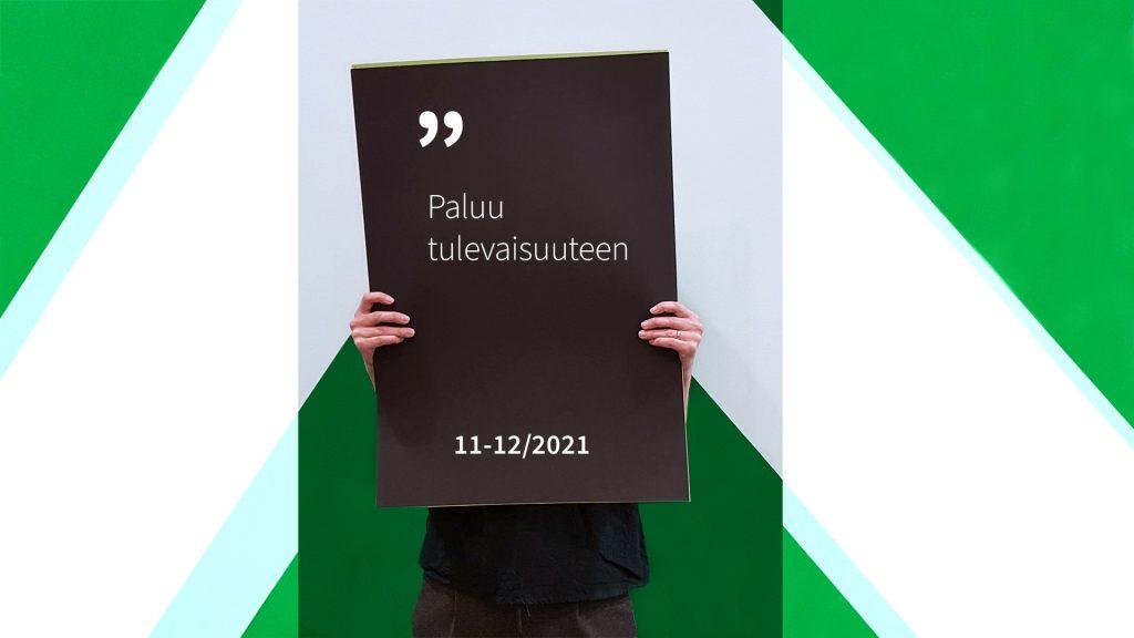 Henkilö pitää käsissään kylttiä, jossa lukee Paluu tulevaisuuteen 11-12/2021.